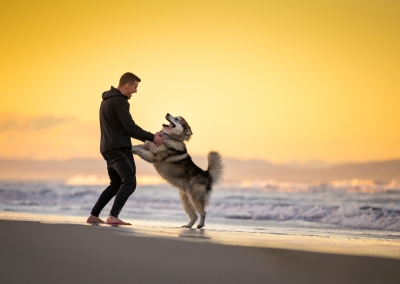 man playing on the beach with his dog